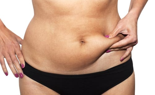 Woman pinching abdomen with her fingers measuring belly fat (shutterstock_98660858)