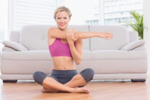 Smiling blonde sitting in lotus pose stretching arms at home