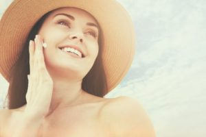 Young woman in hat applying sunscreen on face