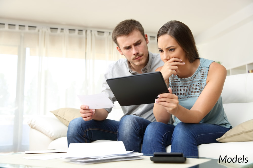 Couple doing research online with concerned facial expressions.